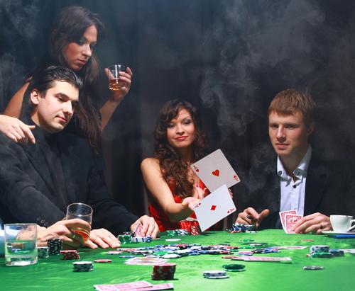 groupe d'hommes et de femmes assis à une table de jeu