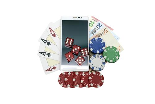 jeu de carte, billet de banque, jetons de casino et plusieurs dés posés sur un smartphone