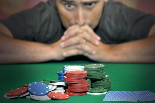 jeune homme qui se concentre en face d'une pile de jeton de casino